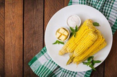Gotowana kukurydza z solą i masłem na białym talerzu. Widok z góry