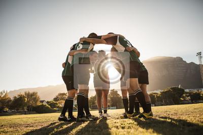 Plakat Gracze rugby skupieni na boisku sportowym