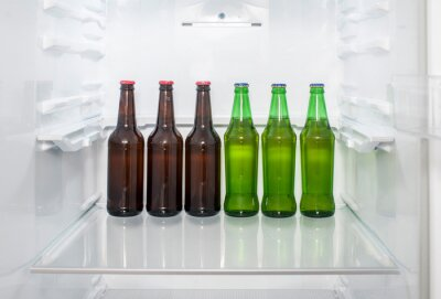 Plakat Green and brown glass beer bottles stand on a shelf in the refrigerator
