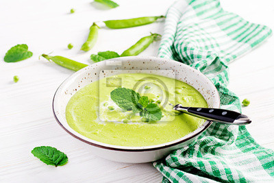 Green pea soup in bowl on wooden table. French cuisine.