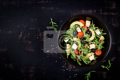 Green salad with sliced avocado, cherry tomatoes, black olives and cheese. Healthy diet vegetarian summer vegetable salad. Table setting. Food concept. Top view.
