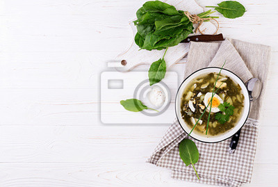 Green soup of sorrel in white bowl. Flat lay. Top view