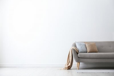 Plakat Grey sofa with pillows near white wall in stylish living room interior. Space for text