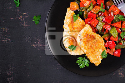 Grilled chicken fillets and sweet pepper on black plate. Top view, copy space