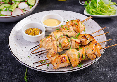 Grilled chicken kebab and salad with cucumber, radish, onion on a dark background.