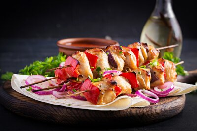 Grilled chicken kebab with paprika on a wooden board.  Grilled meat skewers, shish kebab on dark background.