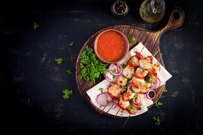 Grilled chicken kebab with paprika on a wooden board.  Grilled meat skewers, shish kebab on dark background. Top view, overhead, flat lay