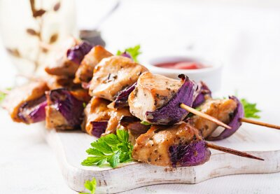 Grilled chicken kebab with red onions on a light table. Grilled meat skewers, shish kebab on light background.