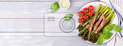 Grilled green asparagus wrapped with bacon on wooden table. Banner. Top view