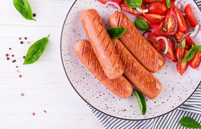 Grilled sausage with tomatoes, basil salad and red onions. BBQ menu. Top view