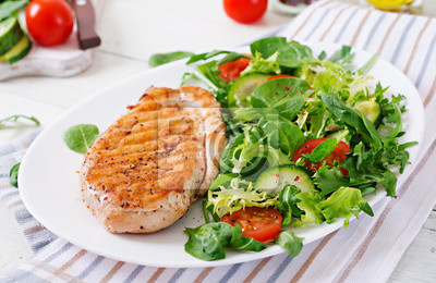 Grillowana pierś z kurczaka i sałatka ze świeżych warzyw - pomidory, ogórki i liście sałaty. Sałatka z kurczakiem. Zdrowe jedzenie.