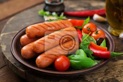 Grillowane kiełbaski i warzywa na drewnianym tle w stylu rustykalnym.