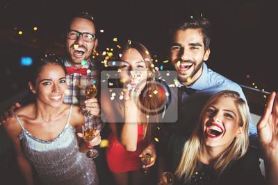 Plakat Grupa osób biorących imprezę, dmuchanie konfetti