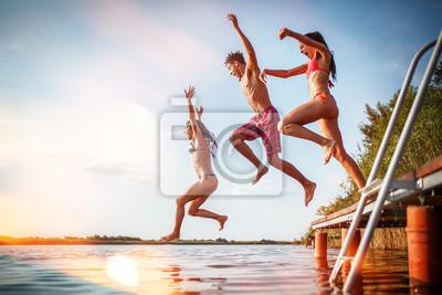 Plakat Grupa przyjaciele skacze w jezioro od drewnianego pier.Having zabawy na letnim dniu.