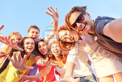 Plakat Grupa szczęśliwy młodych przyjaciół robienie autoportretów na tle błękitnego nieba.