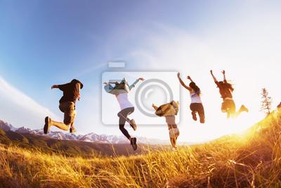 Plakat Grupowi szczęśliwi przyjaciele biegają i skaczą góra zmierzch