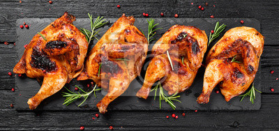 Plakat Halves of appetizing grilled juicy chicken with golden brown crust served with lemon slices,barbeque  sauce and rosemary.