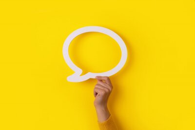 Plakat hand holding dialogue bubble over yellow background