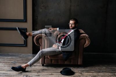 Plakat handsome elegant businessman posing in armchair, hat lying on floor near, loft interior