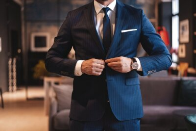 Plakat Handsome man adjusting his jacket while standing in modern office.