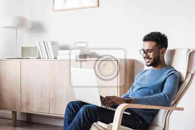 Plakat Handsome young man using laptop computer at home. Student men resting in his room. Home work or study, freelance concept