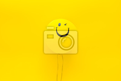 Plakat Happiness emotion. Yellow balloon with smile on yellow background top view copy space