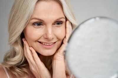 Plakat Happy 50s middle aged woman model touching face skin looking in mirror. Smiling mature older lady pampering, enjoying healthy skin care, aging beauty, skincare treatment cosmetic products concept.