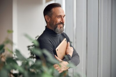 Plakat Happy adult caucasian man is working in a modern office