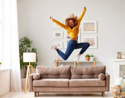 Plakat Happy african american teen girl jumping on sofa while having fun on weekend at home