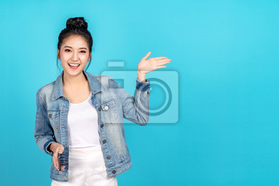 Plakat Happy asian woman feeling happiness and standing hold smartphone other hand open on blue background. Cute asia girl smiling wearing casual jeans shirt and connect internet shopping online and present