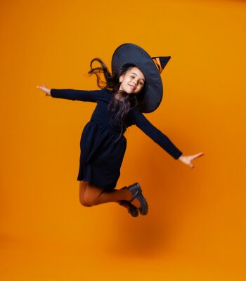 Plakat Happy Caucasian girl in a witch costume jumping on an orange background. halloween.