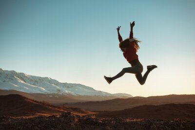 Plakat Happy girl jumps against mountains at sunset
