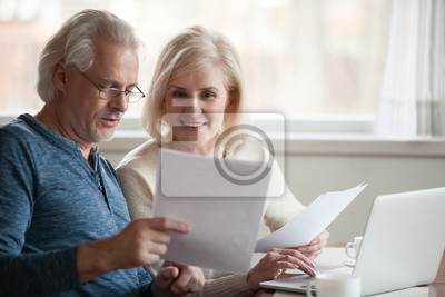 Plakat Happy old middle aged couple holding reading good news in document, smiling senior mature family excited by mail letter, checking paying domestic bills online on laptop, discussing budget planning