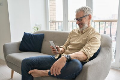 Plakat Happy older middle aged man using apps on phone relaxing sitting on couch at home. Smiling senior hipster with tattoos wearing glasses holding cellphone device ordering delivery online or texting.