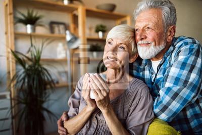 Plakat Happy romantic senior couple hugging and enjoying retirement at home