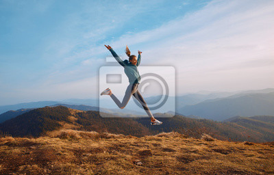 Plakat Happy woman hiker jumping on mountain ridge on blue cloudy sky and mountains background. Travel and active lifestyle concept.