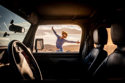 Plakat Happy woman in travel adventure lifestyle summer vacation jump with hoyful and smile outside the car viewed from inside through the door - concept of road trip and female driver - freedom journey life