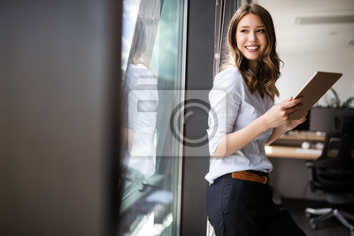 Plakat Happy woman manager holding tablet and standing in modern office