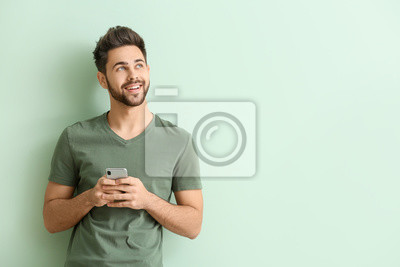 Plakat Happy young man with mobile phone on color background