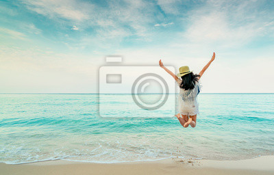 Plakat Happy young woman in casual style fashion and straw hat jumping at sand beach. Relaxing, fun, and enjoy holiday at tropical paradise beach with blue sky and white clouds. Girl in summer vacation.