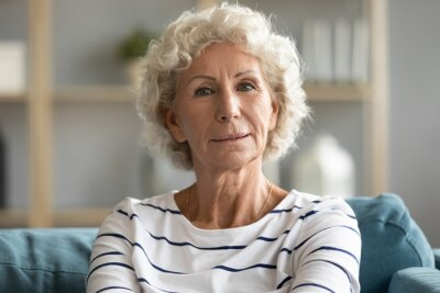 Plakat Head shot portrait close up beautiful aged mature woman with grey curly hair sitting on cozy couch, posing for photo at home, attractive older senior female looking at camera, natural old beauty