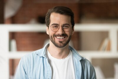 Plakat Head shot portrait confident smiling bearded businessman in glasses looking at camera, standing in office, successful happy young man employee entrepreneur posing for photo or recording video