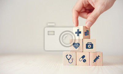 Plakat Health Insurance Concept, Hand arranging wood cube stacking with icon healthcare medical on wood background, copy space, financial concept.