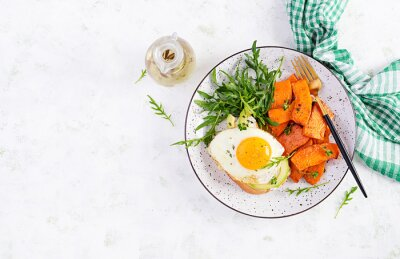 Healthy breakfast. Avocado sandwich with fried egg and fried sliced pumpkin with arugula for healthy breakfast or snack. Top view, overhead, flat lay