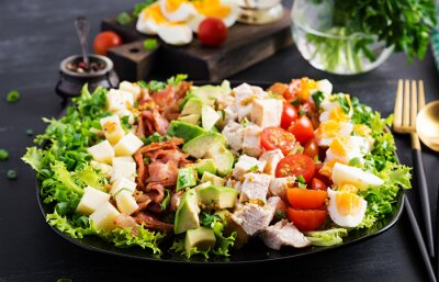 Healthy cobb salad with chicken, avocado, bacon, tomato, cheese and eggs. American food.