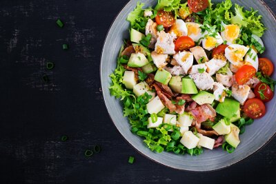 Healthy cobb salad with chicken, avocado, bacon, tomato, cheese and eggs. American food. Top view. Flat lay, overhead