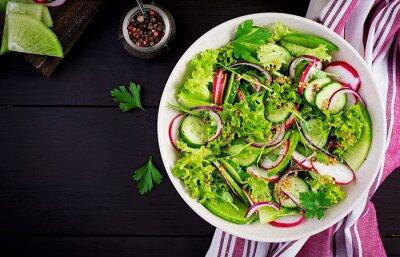 Healthy vegan food. Vegetarian vegetable salad of radish, cucumbers, lettuce  and red onion.  Top view, copy space