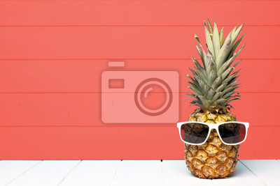 Plakat Hipster pineapple with sunglasses against a living coral colored wood background. Minimal summer concept.