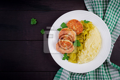 Homemade fried cutlets/meatballs with mashed potatoes and pickled cucumber on white plate. Top view, overhead, copy space.