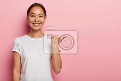 Plakat Horizontal shot of happy young Asian woman points away on copy space, demonstrates something good, wears white t shirt, helps pick best choice, recommends product, models over pink background